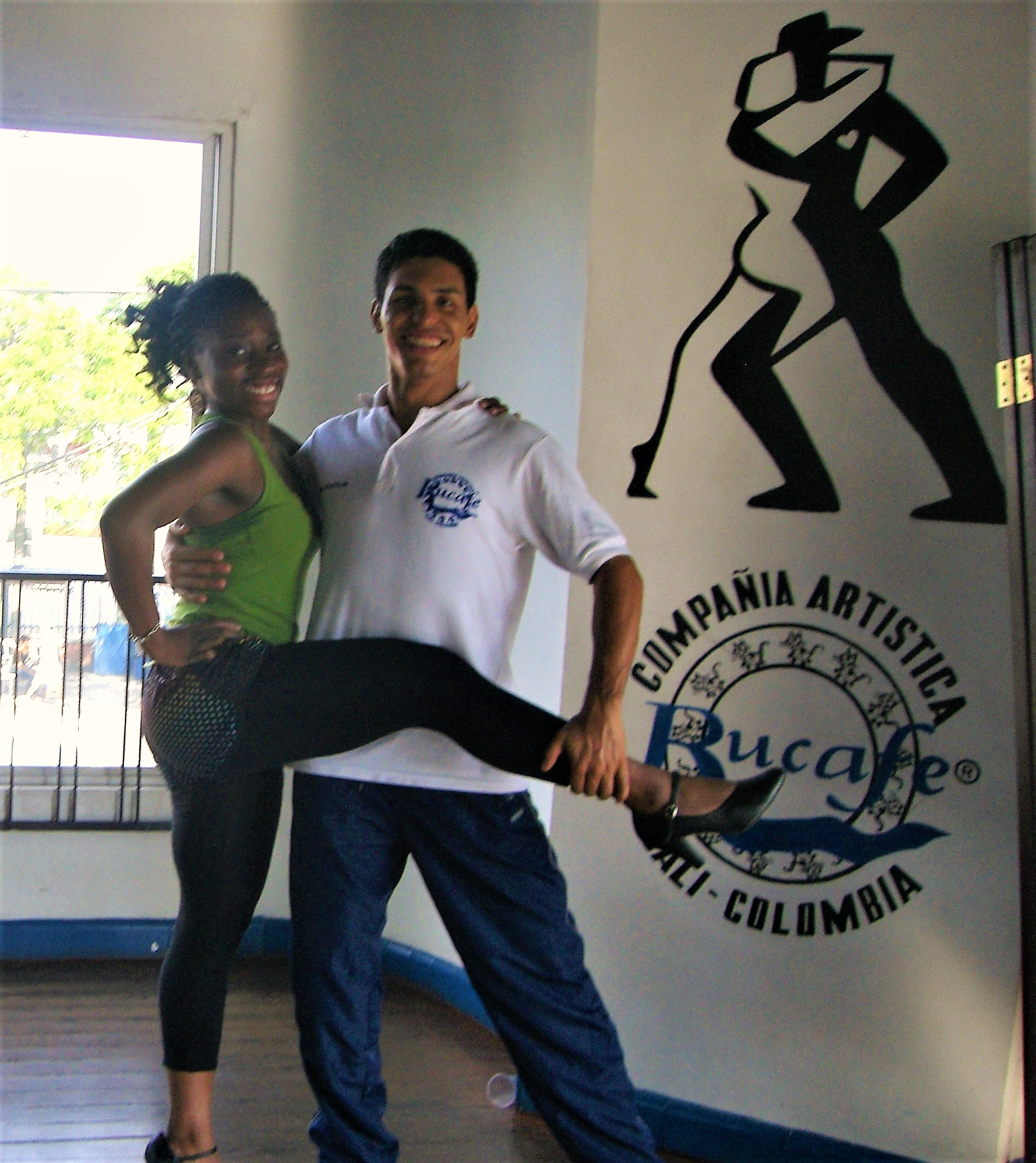 Black girl in a green vest top ad black leggings with right arm on her hips and left arm around the shoulders of her male dance teacher. He holds her right leg whilst she stands on her left foot in a dancing school